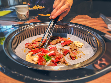 female hand cooking korean bulgogi griller beef in a bbq grill on restaurant table