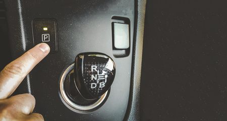 hand finger press park gear button on automatic transmission car interior overhead above view horizontal background film grain