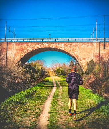 individual jogging marathon in urban park uber the bridge vertical