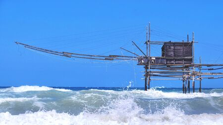 Trabocchi coast in Abruzzo with big waves on rough sea - Italy - a trabucco is an old fishing machines famous in south italy sea