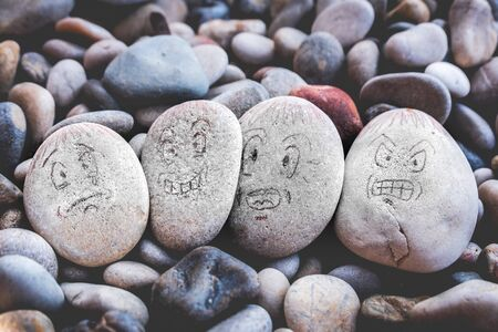 managing emotions emoji faces on stones - sad, happy, surprised and angry draw .