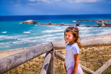 cute sweet nice smart look brat little girl baby wink with colorful summer seascape background