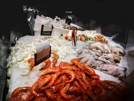 fishmonger bar counter with shrimps , octopus and other fresh seafood