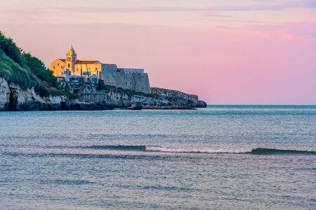 south italy background of Vieste church village at sunset by the sea with purple sky