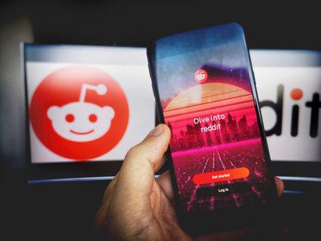 Reddit app smartphone reddit logo screen background . Редакционное