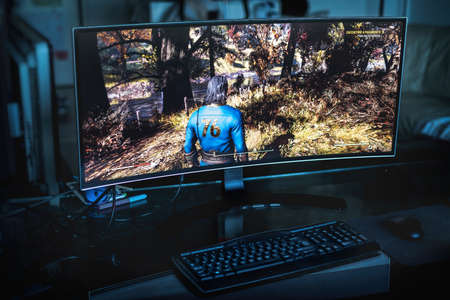 PC gaming concept - an ultrawide screen on a dark room with the Fallout 76 game on it in Bologna, Italy, 04 September 2020 - Illustrative Editorial Редакционное