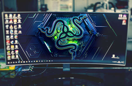 PC gaming concept - an ultrawide screen with the Razer logo on as Windows wallpaper. Razer is a company that make pro gaming gears such as mouses and keyboards