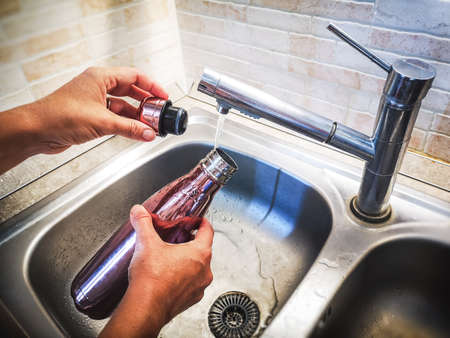 hand with aluminum eco friendly bottle pour tap water from the sink to reduce plastic usage Фото со стока