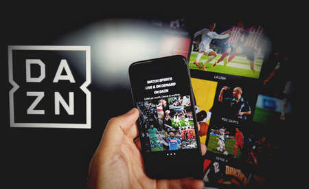 DAZN app for mobile phone with DAZN background - DAZN is a subscription sports streaming service with on demand and live events