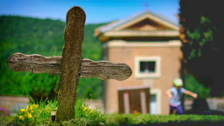 Old wooden cross in the cemetery with a small church on sunny day