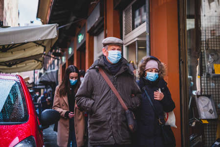 elderly couple old man woman walk italian streets masks face during Covid-19 pandemic in Bologna