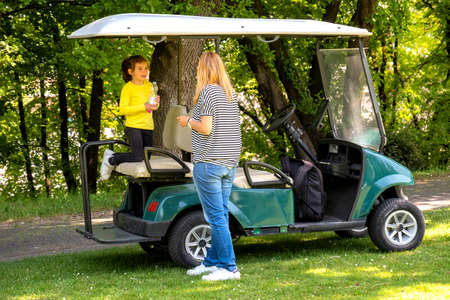 golf cart green buggy family with mother and child in vacation on the golf course Foto de archivo