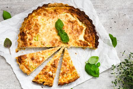 Leek and bacon quiche on a gray surface with fresh basil leaves