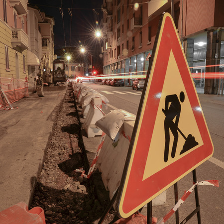 roadwork: road work sign at night with digger trench and traffic