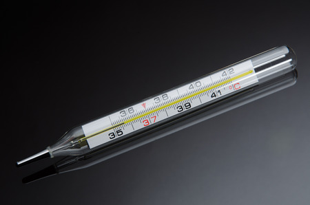 glass thermometer: mercury in glass thermometer on black background with reflection Stock Photo