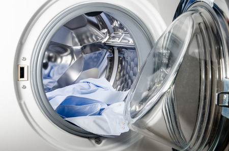 white washing machine loaded with blue shirt
