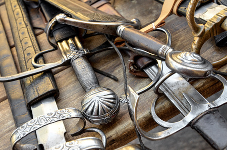 sword: medieval swords on a wood table Stock Photo