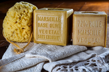 colorant: cubes of marseille natural soap with yellow sponge and white cotton bath towel