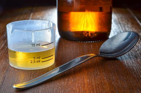 jarabe: dosis de jarabe para la tos amarillo con la taza de medir, cuchara y una botella medicin