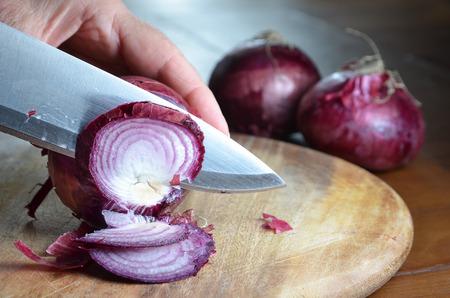 cebolla: cortar cebolla roja con el cuchillo en la tabla de cortar