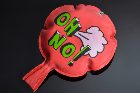 flatulence: red rubber whoopee cushion with reflection on black glass