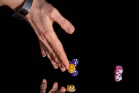 hand of woman who is throwing colored dice Stok Fotoğraf