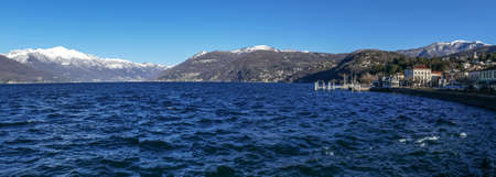 Extra wide view of Luino and Lake Maggiore with snow-capped mountains in the background