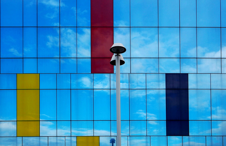 street lamp in front of a reflective  glass facade Stock Photo