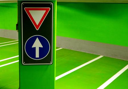 subterranean: street signs ina green subterranean parking