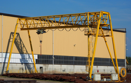 Gantry crane and its shadow on the factory wall. Raw materoals on the floor Editorial
