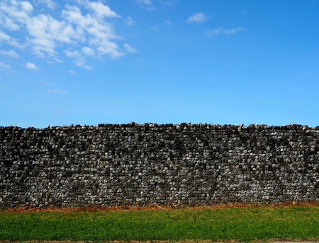 Rural background, Ancient medieval wall with grass and blue sky Stock Photo