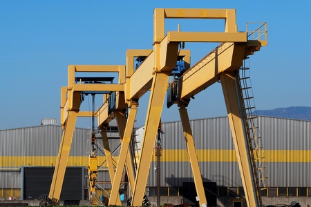 Gantry cranes in front of a gray and yellow building of a manufacturing plant Zdjęcie Seryjne