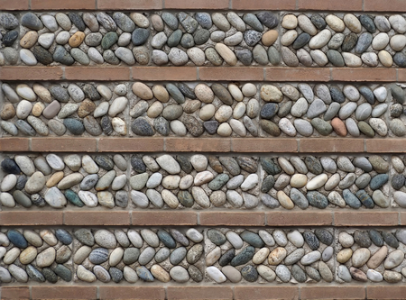 Wall texture. Strips of pebbles interspersed with horizontal bricks. 写真素材