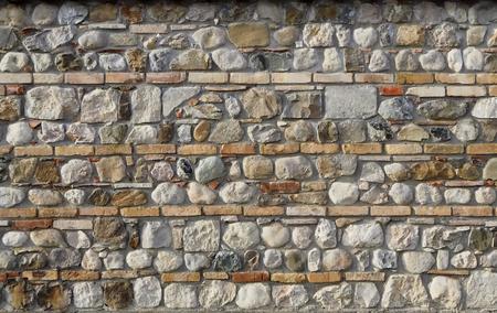 壁の背景。水平レンガのラインが散在する天然石