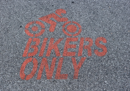 Motorcycle parking only sign, painted in red on asphalt with the silhouette of a motorcycle riding biker
