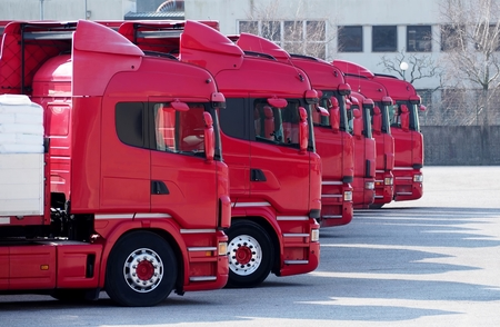 Red trucks lined up in a parking lot, ready to go.
