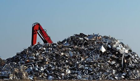 Large stack of aluminum and ferrous materials scrap ready for recycling shines under the sun. Excavator boom on the left