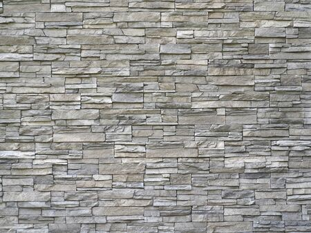 Stone cladding wall made of striped stacked slabs of natural gray rocks. Panels for exterior.