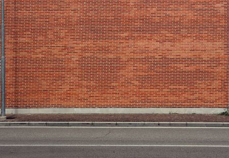 High brick wall and a concrete sidewalk Asphalt road in front. Background for copy space Foto de archivo