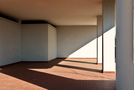 White wall, terracotta tiled floor and columns in the entrance of a residential building. Oblique shadow divides the scene. Background for copy space