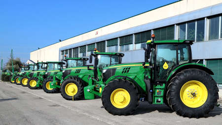 Basiliano, Italy. March 2 2019. Row of brand new John Deere tractors outside the store of local consortium, exhibition of latest agricultural machinery.