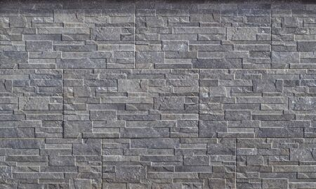 Stone wall cladding made of embossed horizontal gray stripes of rock stacked in panels .Background and texture.