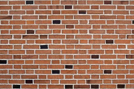 Wall made with brown bricks mixed randomly with small black ones. Background and texture with copy space
