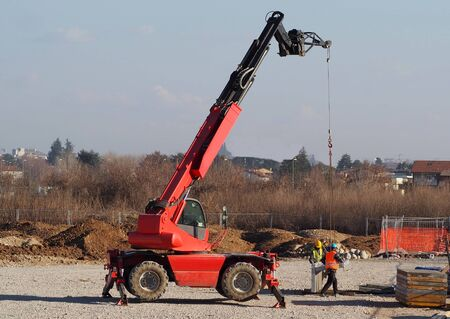 Two workers with a telescopic handler loader assemble concrete slabs for the new building in the construction site. Stock Photo