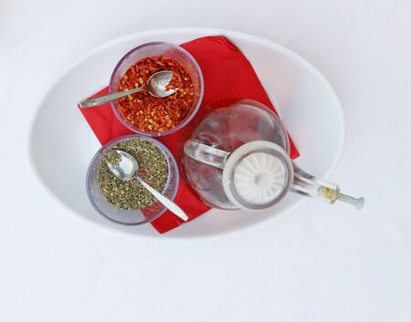 Seasonings to flavor the freshly baked pizza in Italy. Spicy oil, ground flavored herbs and ground chili pepper.