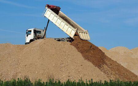 Dump truck unloading soil on the top of dunes