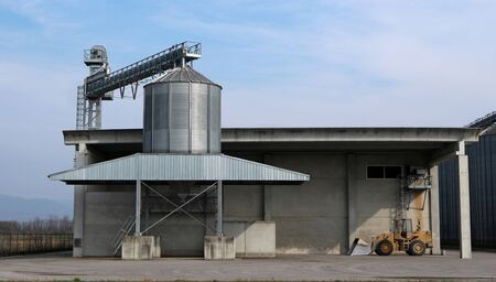 Small steel granary silo with conveyor belt in a concrete agricultural building.