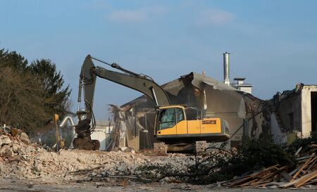 Excavator among debris and dust demolishes the old house for an urban redevelopment