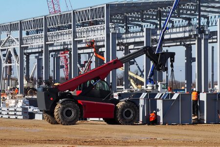 Telescopic handler at work in a large construction site. Intense building activity on background Stock Photo
