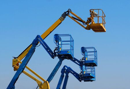 Work aerial platforms against blue cloudless sky. One cherry picker yellow among three blue Imagens